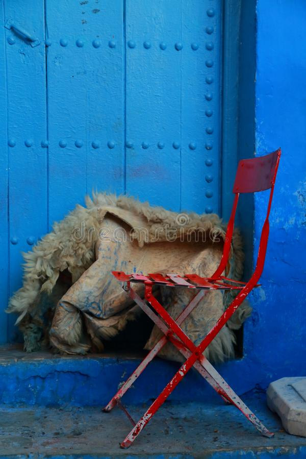 Chaise et peau de mouton rouges devant une porte bleue images stock