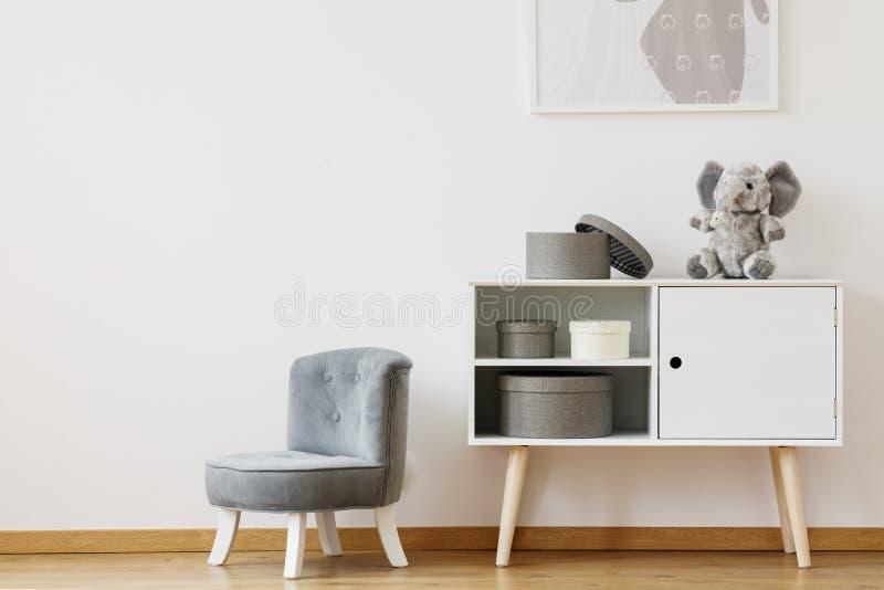 Chaise grise à côté de l'étagère blanche images libres de droits