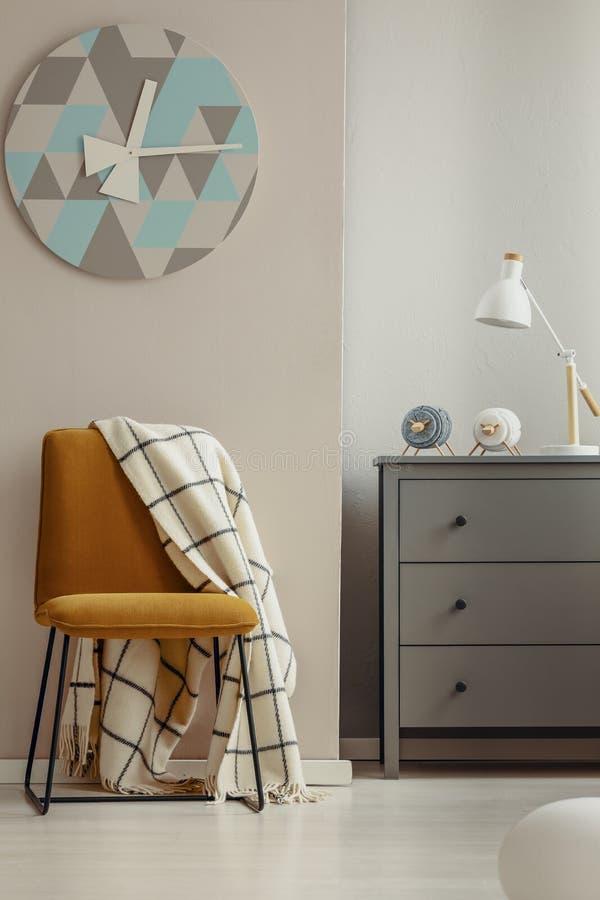 Chaise jaune élégante dans l'intérieur élégant avec le coffre des tiroirs en bois gris image stock