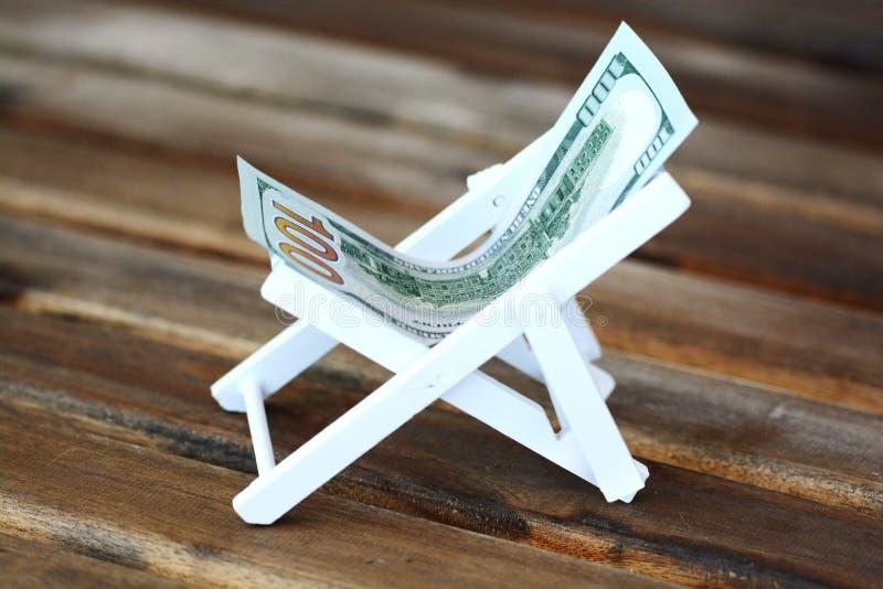 Chaise länge eller solstol som göras av oss dollar på träbakgrund, pengar för semesterbegrepp royaltyfria bilder