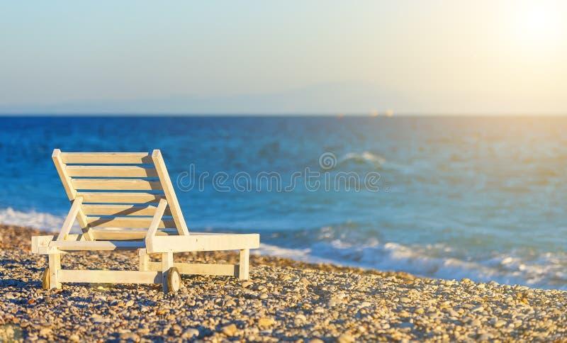 Chaise longue di legno bianche sulla riva di Pebble Beach al tramonto, sfuocatura, profondità di campo fotografia stock libera da diritti