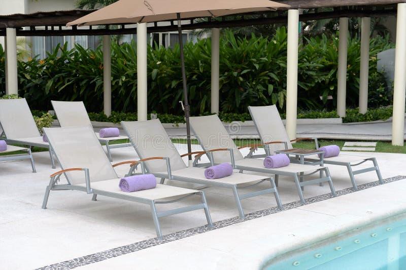 Chaise loung stoelen naast pool stock afbeeldingen