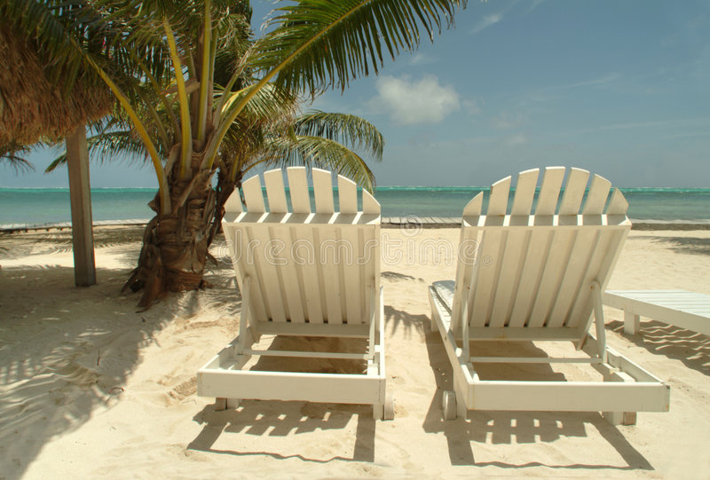 Chaise lounge chairs on a tropical beach. stock photo