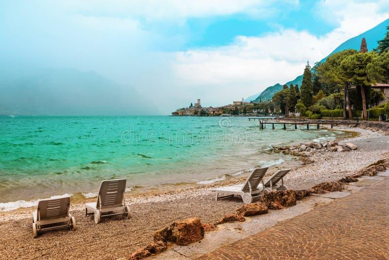 Chaise-lounge della spiaggia al gardasee della riva del lago con acqua ondulata, malcesine fotografia stock