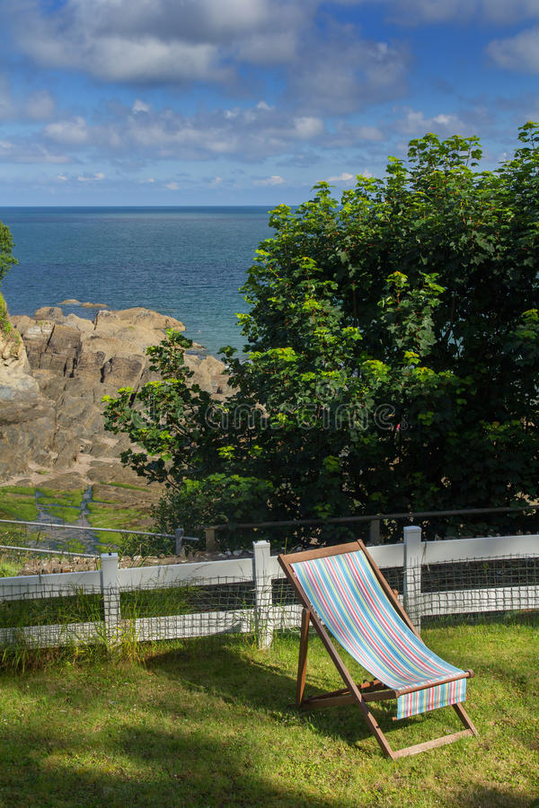Chaise lounge on the green lawn. Excellent View of the Bay of Combe Martin royalty free stock photo
