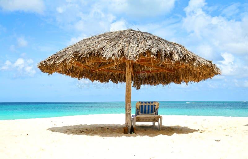 Chaise-lounge sotto la cabina, parasole Acqua di mare blu e nuvole drammatiche Oranjestad, Aruba Eagle Beach famoso fotografie stock