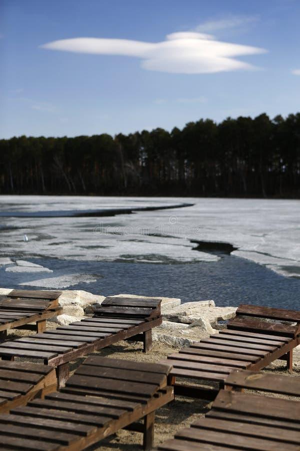 Chaise-lounge vuote sulla spiaggia mentre ghiaccio sul lago fotografia stock