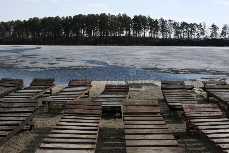 Chaise-lounge vuote sulla spiaggia mentre ghiaccio sul lago fotografie stock
