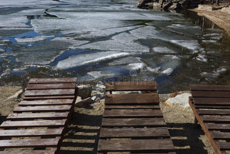 Chaise-lounge vuote sulla spiaggia mentre ghiaccio sul lago immagini stock