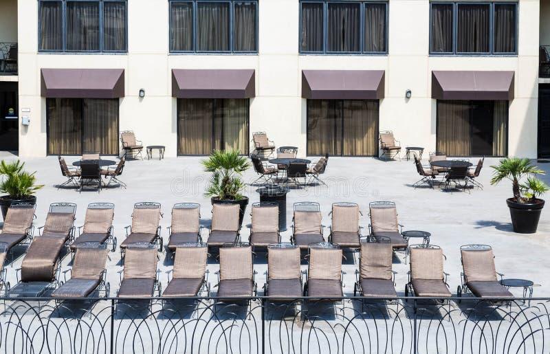 Chaise Lounges no pátio do hotel fotografia de stock royalty free