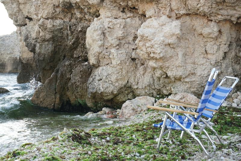 Chaise lounges for sunbathing on the stone Sea Beach royalty free stock photos