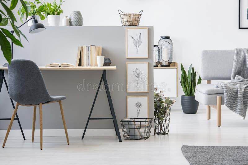 Chaise moderne avec les jambes en bois par un bureau industriel avec les livres b photos stock