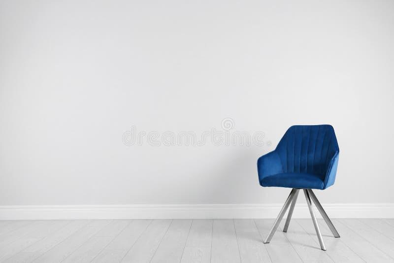 Chaise moderne bleue pour la conception intérieure sur le plancher en bois au blanc photo libre de droits
