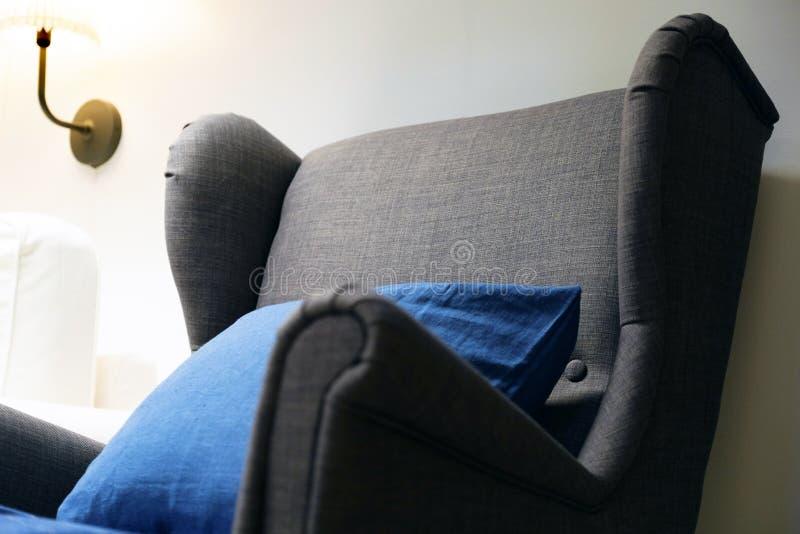 Chaise molle bleue avec l'oreiller, haute lampe de lecture arrière au-dessus de la tête Intérieur de salle de séjour Sofa avec de image stock