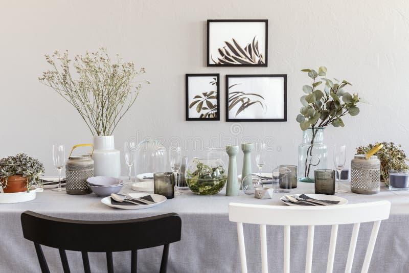 Chaise noire et blanche à la table avec la vaisselle dans l'intérieur gris de salle à manger avec des affiches photos libres de droits