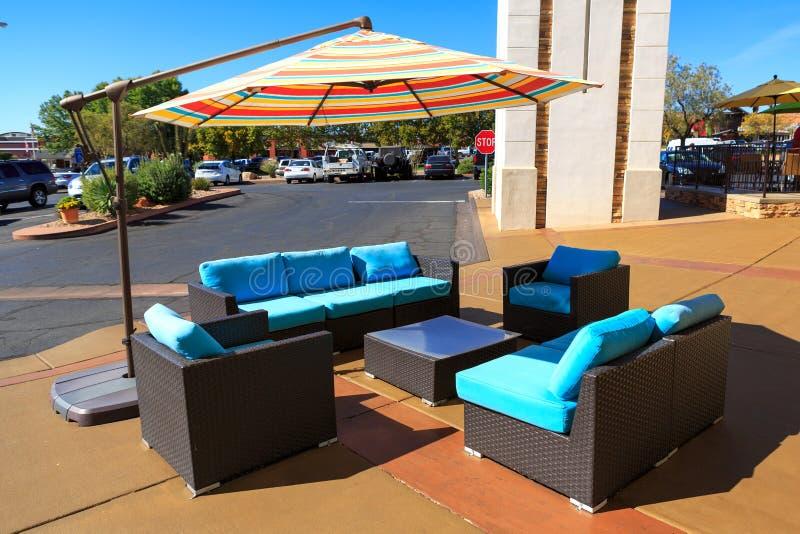 Chaise noire et bleue et table artificielles de rotin extérieures avec du Bi photographie stock