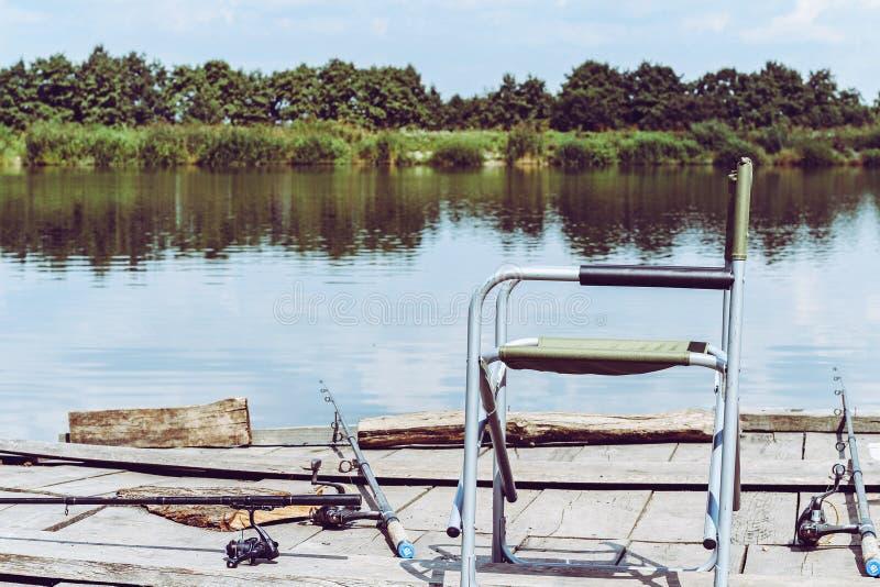 Chaise pliante, tige pour pêcher sur le pilier en bois à la rive R?tro photo modifi?e la tonalit? d'?quipement de p?che photographie stock libre de droits