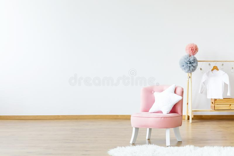 Chaise rose avec le coussin en forme d'étoile se tenant dans la pièce lumineuse de bébé photo libre de droits