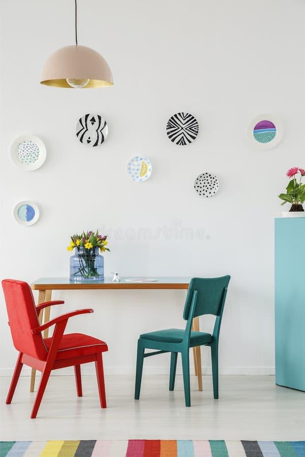 Chaise rouge et verte, plats comme décoration de mur, lampe, table avec image stock