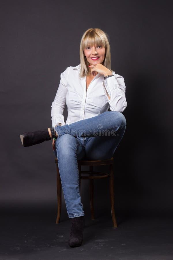 Chaise se reposante de sourire mûre de la femme 40s photos libres de droits