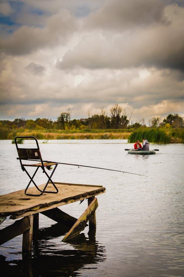 Chaise sur le dock avec une canne à pêche photographie stock libre de droits