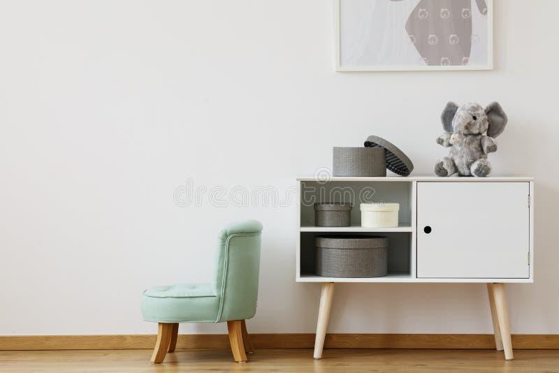 Chaise verte à côté de l'étagère blanche photos stock