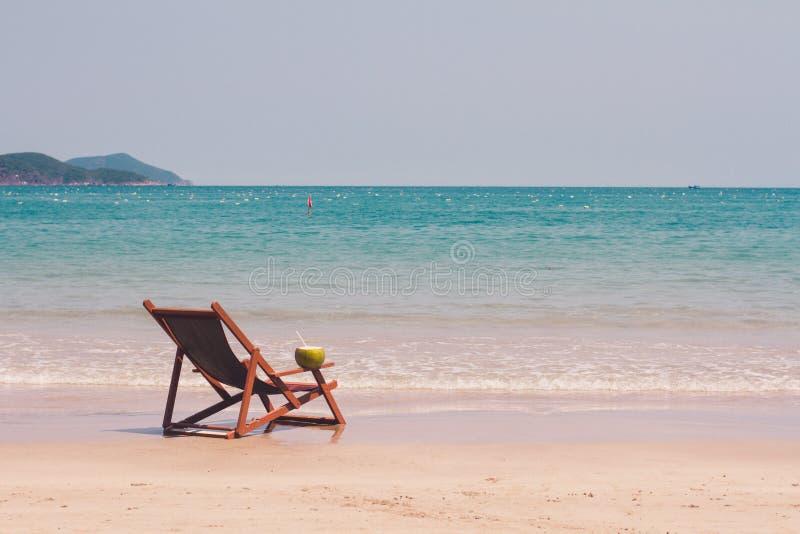 Chaise zitkamer op het strand tegen het overzees stock foto