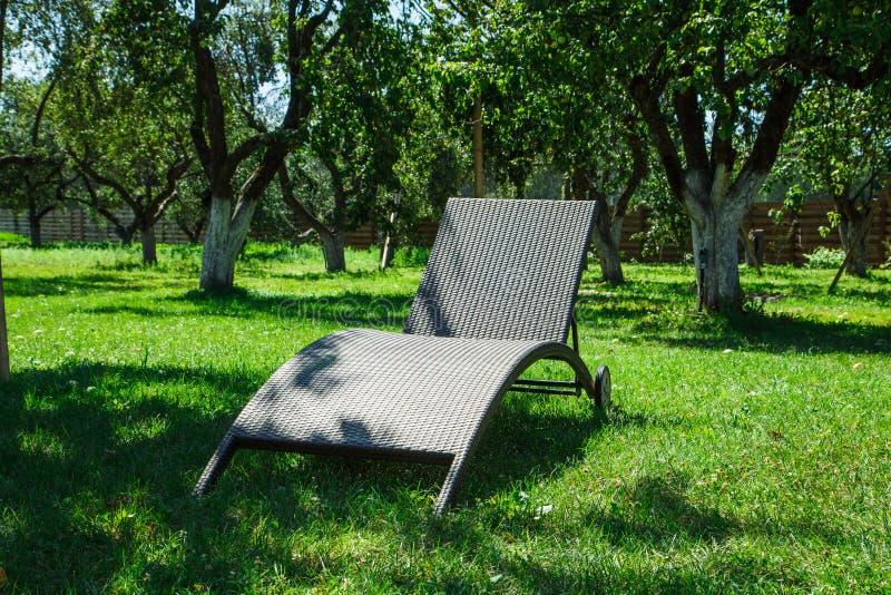 Chaise zitkamer op het zonnige gazon stock foto
