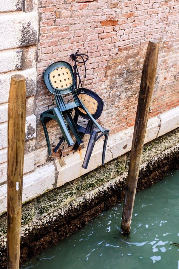 Chaises accrochant sur le mur de briques au-dessus du canal de Venise l'Italie, l'Europe photos libres de droits