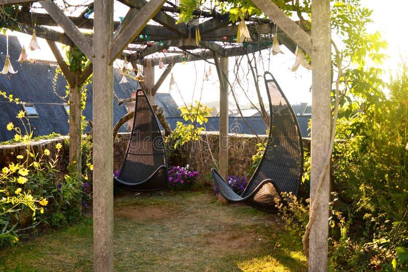 Chaises accrochantes d'osier dans le jardin avec le fond vert de nature photo libre de droits