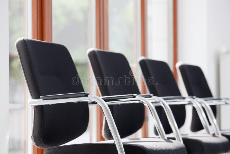 Chaises alignées dans une salle d'attente ou un salon ensoleillé photographie stock libre de droits