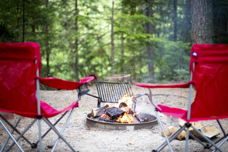 Chaises autour du feu de camp photographie stock
