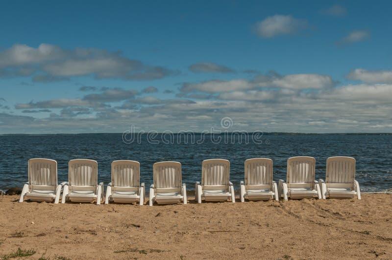 Chaises blanches alignées sur un au bord du lac arénacé images stock