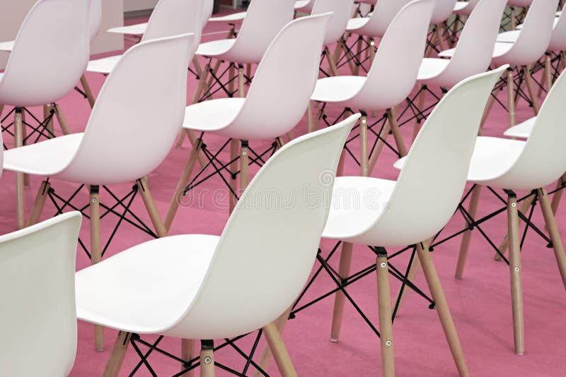 Chaises blanches de conférence dans la chambre d'affaires, rangées des sièges confortables en plastique blancs dans le bureau d'e photo libre de droits