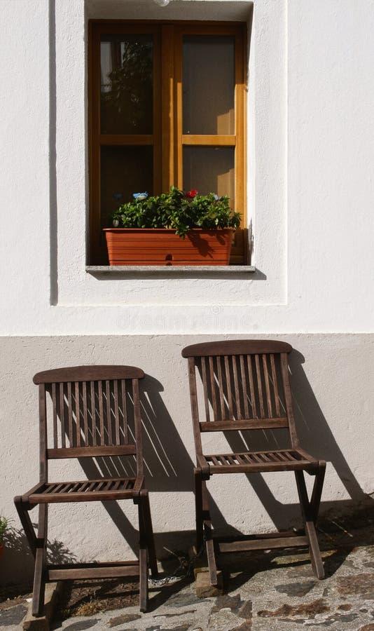 Chaises colorées et froides en dehors d'une maison photographie stock libre de droits