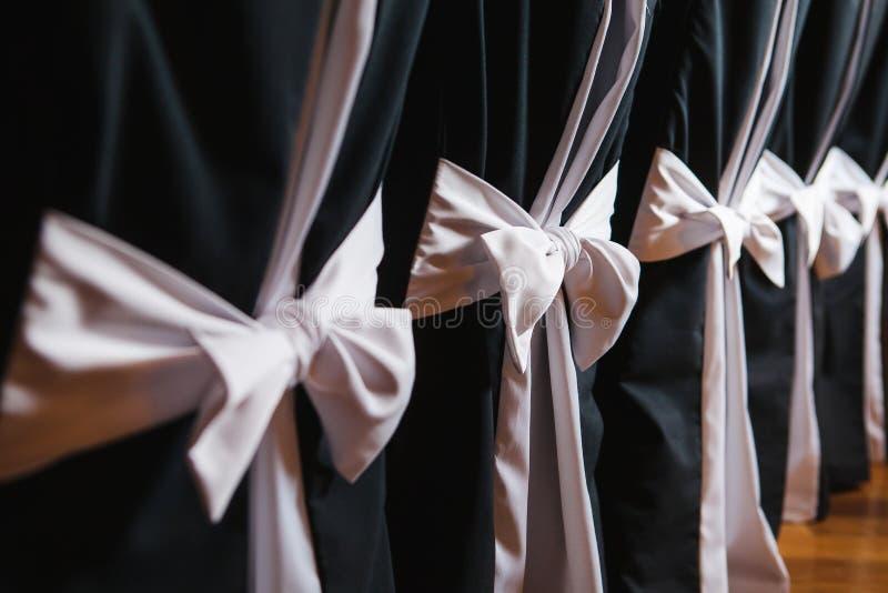 Chaises décorées avec le tissu noir et les grands arcs roses de satin photographie stock libre de droits