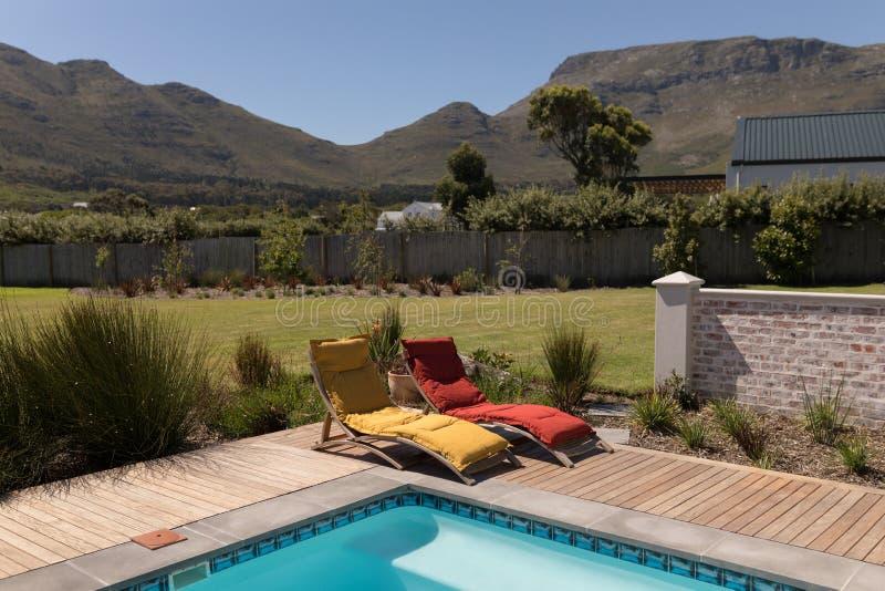 Chaises de canapé de Sun à l'arrière-cour de la maison photos libres de droits