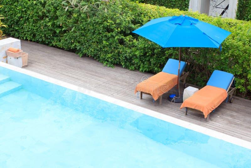 Chaises de détente à coté de piscine images libres de droits