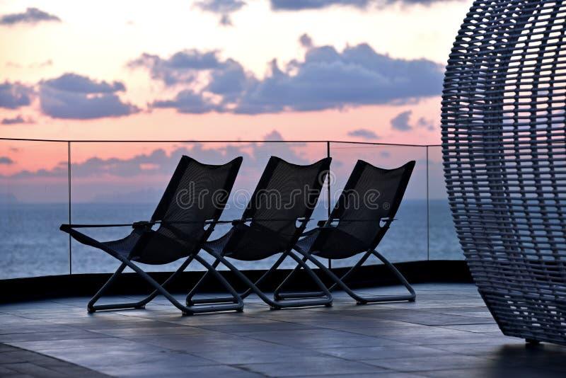 Chaises de détente de coucher du soleil images libres de droits