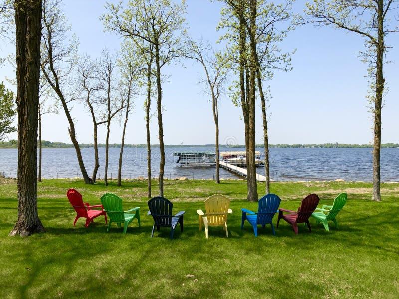 Chaises de jardin colorées sur l'herbe verte près du rivage de lac photos stock