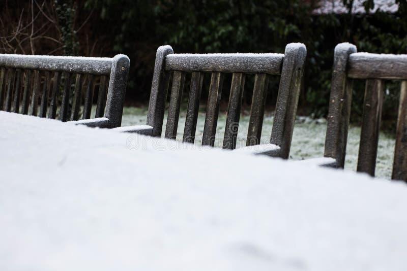 Chaises de jardin confortables en bois couvertes dans la neige dans un jardin d'arrière-cour photo stock