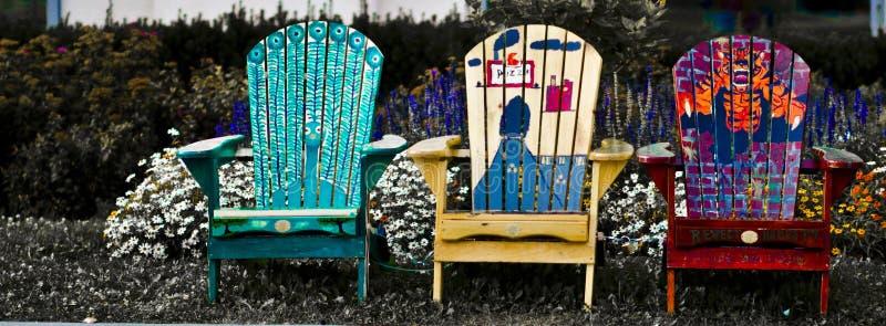 Chaises de jardin devant un lit de fleur photos stock