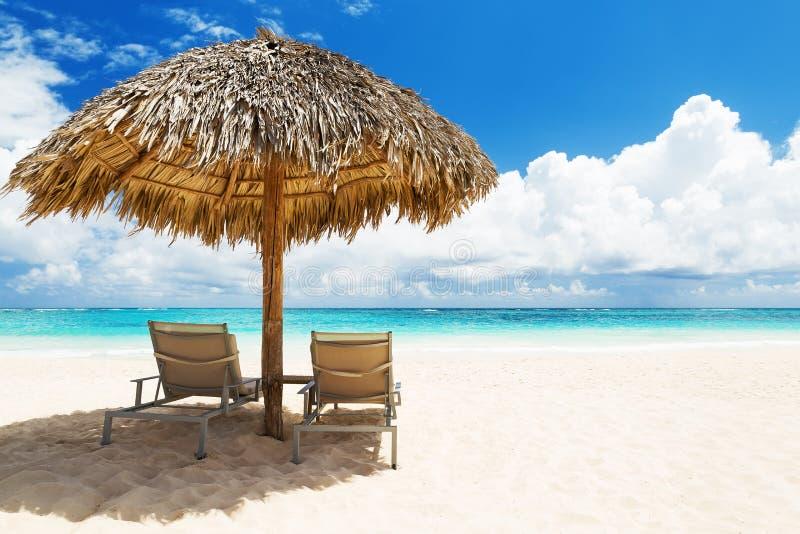 Chaises de plage avec le parapluie et la belle plage de sable dans la boîte de Punta photos libres de droits