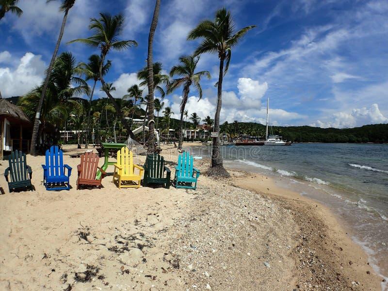 Chaises de plage colorées, palmiers, voiliers attachés jusqu'au dock, et belle plage de sable images libres de droits