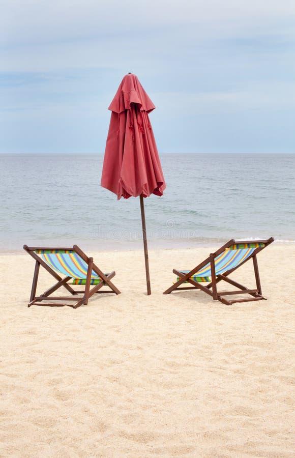 Chaises de plage et un parapluie sur une plage vide photos libres de droits