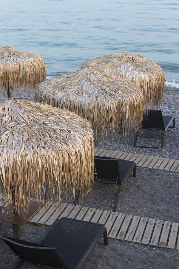 Chaises de plage sur la plage de sable de caillou au coucher du soleil photographie stock