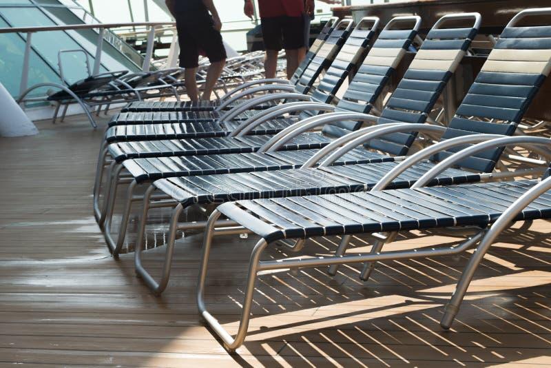 Chaises de plate-forme de bateau de croisière exposant au soleil et détendant photo stock