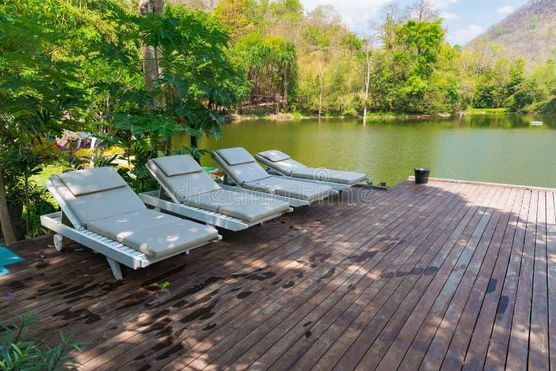 Chaises de plate-forme en bois sur le plancher en bois près du bleu de lac et de montagne photographie stock