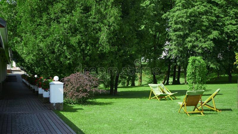 Chaises de repos dans le jardin Concept de station de vacances image libre de droits