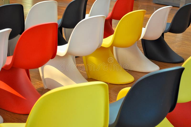 Chaises en plastique colorées alignées dans une chambre image stock
